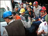 Rescue workers carry bodies of miners