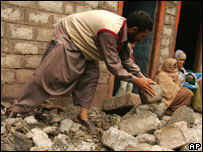 A quake survivor clears rubble from his devastated house