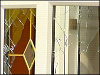 Smashed window in house raided by police