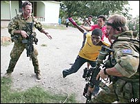 Australian soldiers pull a man away as they attempt to check a rival gang member for weapons in Dili