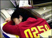 A worker naps at their desk