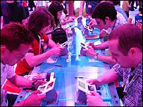 People playing the Nintendo DS Lite at E3
