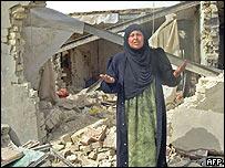 Una mujer frente a  ruinas en Ishaqi.