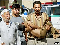 An Iraqi man carries his wounded son after a bomb attack