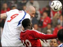 Jan Koller (l) beats Dwight Yorke to a header