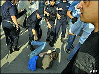 Riot police beat an anti-gay protester in Bucharest