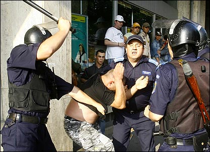 Police beat a protester in Bucharest