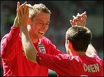Peter Crouch celebrates a goal with Michael Owen