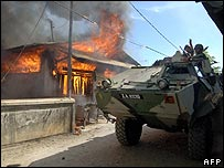 Malaysian peacekeepers drive past a burning house in Dili on Sunday