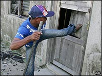 Assailant kicks down door of rival gang member's house in Dili, East Timor on Sunday