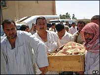 People carrying a coffin of one of those killed in Iraq
