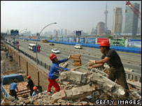 Workers in Shanghai demolish old buildings to make way for a new convention centre in May