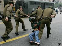 Police officers drag away a student protester in Santiago on 1 June
