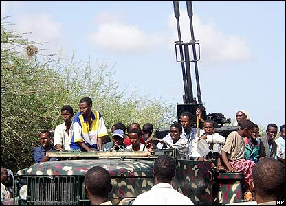 Islamic militia sit on a truck carrying an anti-aircraft gun they seized from the warlords