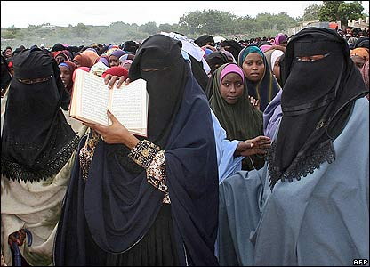 A woman holds a copy of the Koran during a protest against alleged US backing for the warlord alliance on 4 June 2006