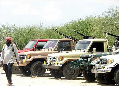 An Islamic militia member walks past vehicles seized from the warlords