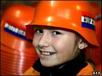 A girl models a replica German World War II helmet, aimed at a Dutch market