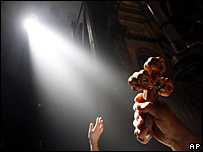 A worshipper holds a cross up to the light