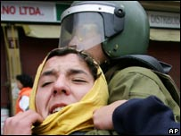 Riot police officer detains a student during demonstrations on 1 June