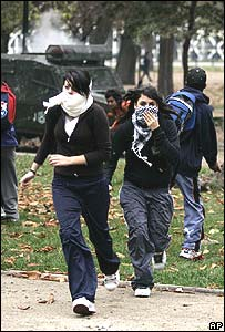Students run as police fire teargas in Santiago