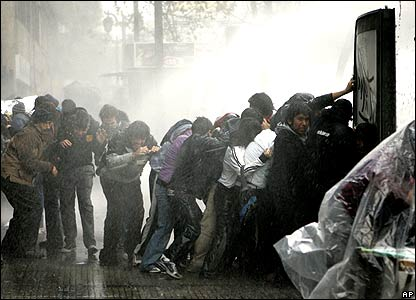 Protesters take shelter from a water cannon