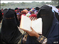 Women in veils holding the Koran