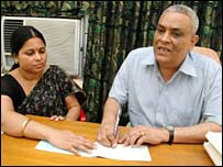 Prasanna Kumar Pincha signs a cheque with help from a colleague