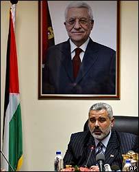 Hamas' Ismail Haniya under a poster of Fatah's Mahmoud Abbas