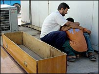 Iraqis mourn at the entrance of a morgue in a local hospital in Baghdad