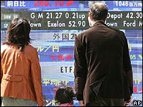 Family looking at screen showing stock market data