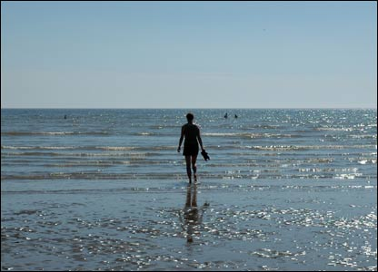 Darran Jones' partner Corinne walking into the sea at Pembrey
