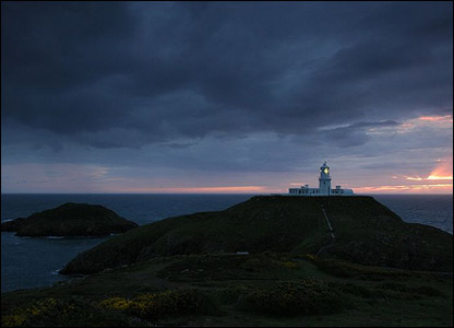 Strumble head of the sunset behind the lighthouse and rain clouds (James Davis)