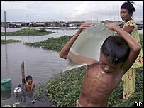 Boy carrying water from the Mekong river in Phnom Penh