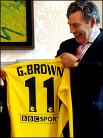 Chancellor of the Exchequer Gordon Brown displays a Your Game shirt