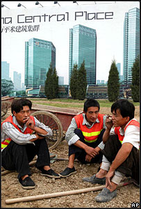 Chinese workers take a smoke break near a billboard advertising new office complexes in Beijing
