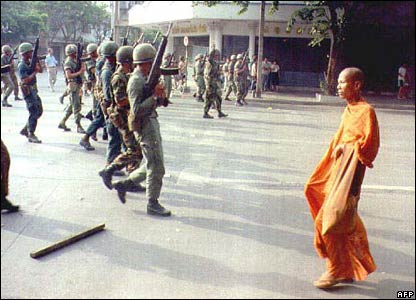 A monk walks past soldiers during protests in Bangkok in May 1992