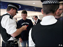 Police at Heathrow Airport check England football fans