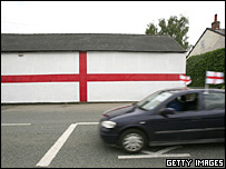 A car with England flags drives past a house with the St George's Cross painted on it