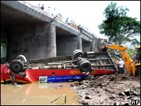 An upturned bus that fell off a bridge into the Chena river in the Indian state of Maharashtra, killing some 26 people