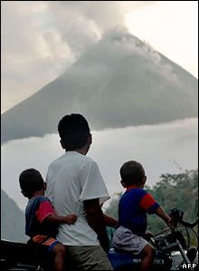 A father and his two sons watch the smoke rising from Mt Merapi on 4 June