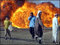 Iraqis walking past burning oil pipeline near Taji in Iraq