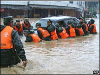Police try to move a submerged car in Nanping, Fujian