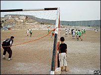 A football match in the West Bank village of Abu Dis, beside the Israeli separation barrier
