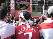 England football fans watching a game on an outdoor screen in Leeds