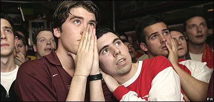 Hombres mirand f�tbol en un pub