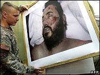 A US soldier holds up a picture of the dead Zarqawi