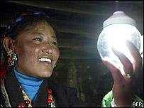 Mujer tibetana observa la luz generada por paneles solares, financiados con proyectos de ayuda