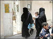 Two women, believed to be sisters of Abu Musab al-Zarqawi, enter his home in Zarqa, Jordan, on Thursday