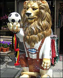 Model of lion holding a football