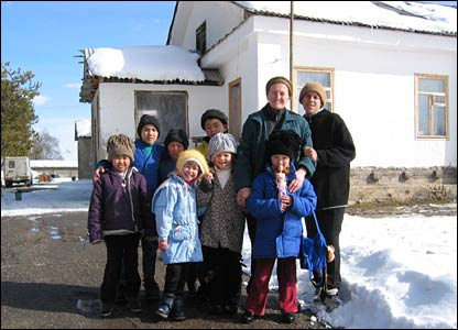 A woman with a group of children, with the orphanage in the background.